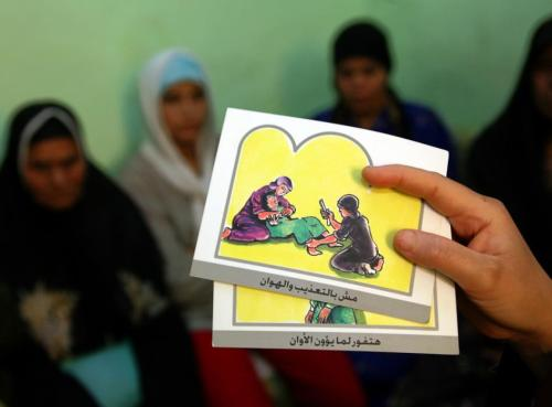 A counsellor holds up cards used to educate women about female genital mutilation (FGM) in Minia June 13, 2006. The practice of FGM dates back over two thousand years in Egypt and is widely practiced in all levels of society for Muslims and Christians alike. Many organizations like UNICEF have funded programs to help educate people about the risks and dangers of FGM in order to change people's opinions on this procedure which is seen by many as a necessary social norm.(REUTERS/STR)