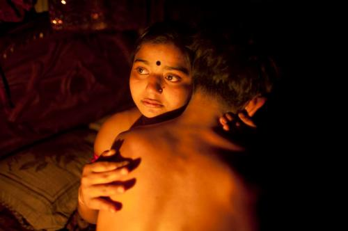 "Seventeen-year-old prostitute Hashi, embraces a Babu, her ""husband"", inside her small room at Kandapara brothel in Tangail, a northeastern city of Bangladesh on March 4, 2012. Many young and inexperienced prostitutes have ""lovers"" or ""husbands"" who normally live outside the brothel occasionally taking money and sex from them in exchange for security in this male dominated society. She earns about 800-1000 taka daily ($9.75 - $12.19) servicing around 15-20 customers every day. Hashi is one of hundreds of mostly teenage sex workers living in a painful life of exploitation in Kandapara slum's brothel who take Oradexon, a steroid used by farmers to fatten their cattle, in order to gain weight and appear ""healthier"" and more attractive to clients. (REUTERS/Andrew Biraj)"